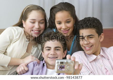 Four teenagers posing for picture