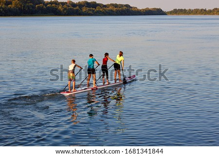 Four teenagers row on a large stand up paddle board on the Danube river at summer Stock fotó ©