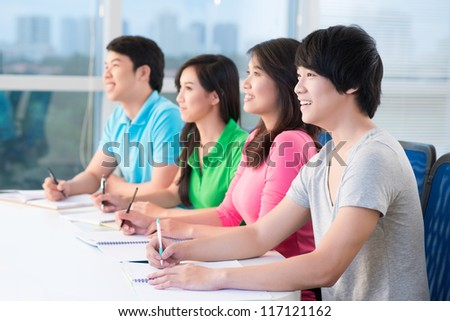 Four teenagers sitting at seminar and listening to teacher