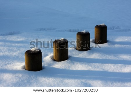 Four telegraph pole stumps poking out of the snow #1029200230