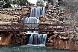 Four tier water fall surrounded by rocks with walking bridge in Wichita Falls Texas.