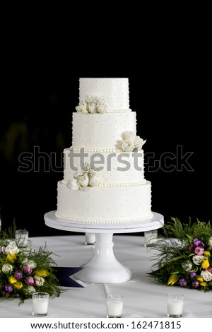 four tiered white wedding cake with black background