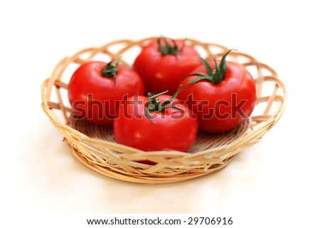 Four tomatoes in a basket against white background