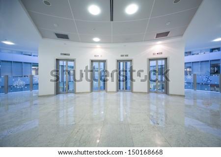 Four transparent elevator door in the business building with marble floor