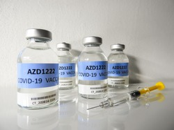 Four transparent glass vials with a test COVID-19 vaccine, named AZD1222, and a glass syringe with yellow piston on a white surface and with white background. Selected focus.