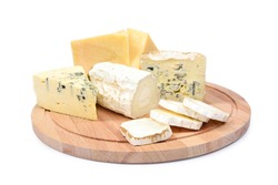 Four types of cheese on a round wooden board isolated on white background. Ripe parmesan, goat cheese with white mold, roquefort and dorblu.