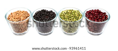 Four types of legumes in glass containers, lentils, black beans, split peas, and red beans. Isolated on a white background