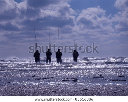 Four unidentifiable fisherman during a heavy evening storm with a bright sunset at the Outer Banks in North Carolina