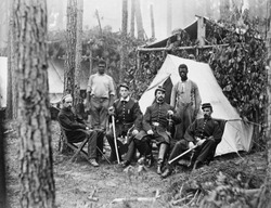 Four union officers in front of tent, with two Africans-American during the Petersburg Campaign. Many former slaves, emancipated in 1863, were employed a servants to Union officers. August, 1864.