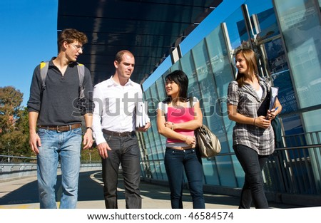 Four university students walking to class over a modern bridge on a beautiful sunny day