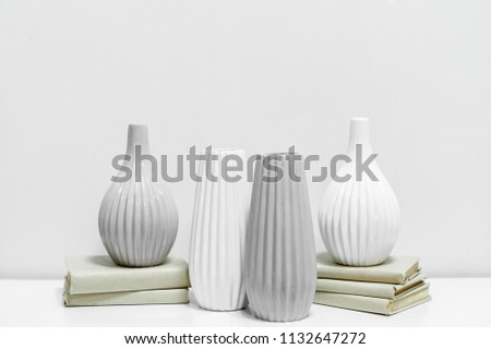 four vases on books; vases with books on a gray background; two white and two gray vases; vases with a narrow and wide neck; four empty vessels  #1132647272