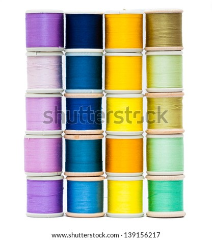 Four vertical stacks of vintage sewing threads isolated on white with shades of purple, blue, yellow and green