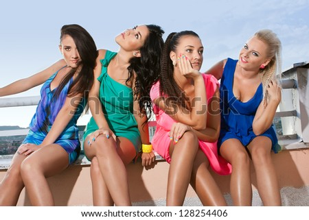 Four very sexy women leaning on a fence