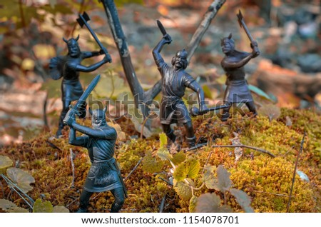 Four Vikings (vintage toy soldiers) who keep the defense on a moss-grown hill, trees and branches in the background, autumn colors, close-up, selective focus, Old Norse myths and sagas the