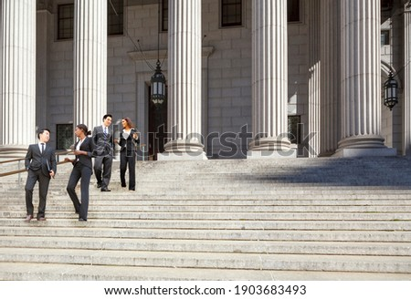 Four well dressed professionals walk down steps in discussion outside of a courthouse. Could be lawyers, business people etc. Stock photo ©