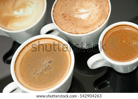 four white coffe cups on the black background