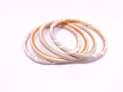 Four white colored Bangles isolated on white background. Bangles are traditionally rigid bracelets, originating from the Indian subcontinent, which are usually made of metal, wood, glass or plastic.