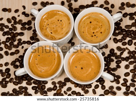 Four white cups with hot coffee on a bamboo tile and bean