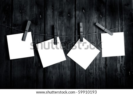 four white papers on a wooden background in black and white