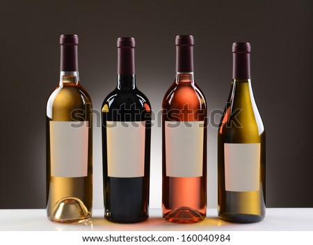 Four Wine Bottles with blank labels on a light to dark gray background. Four different wines including: Cabernet Sauvignon, Chardonnay, Sauvignon Blanc, and White Zinfandel. #160040984