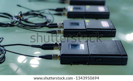 Four wireless microphone transmitter and four wireless microphone reciever on glass table in tv studio