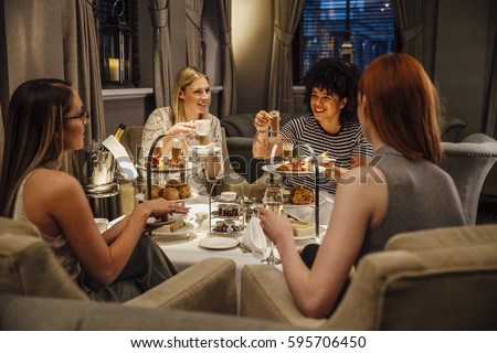Four women are sitting together enjoying afternoon tea. They are talking and eating and they have champagne and tea.