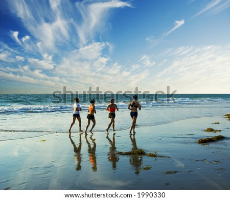 four women go jogging on the beach along the waters edge