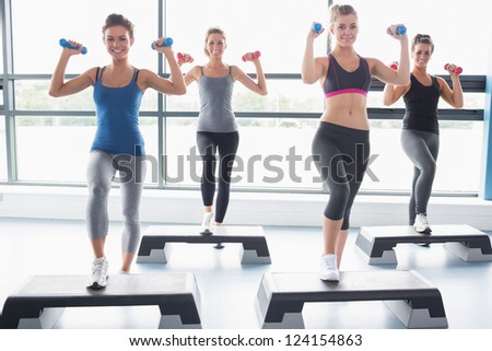 Four women lifting weights while doing aerobics in gym - stock photo