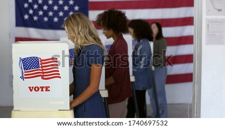 Four women of various demographics, young blonde woman in front, filling in ballots and casting votes in booths at polling station, US flag on wall at back. Focus on booth signage
