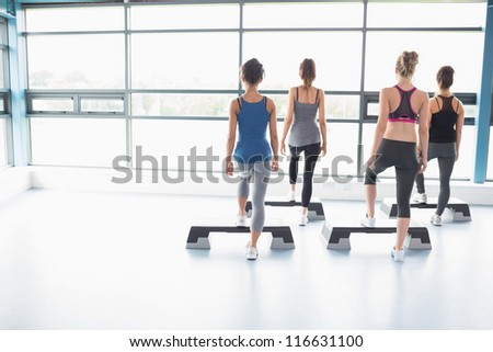 Four women stepping on boards in gym