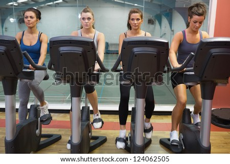Four women working out at spinning class in gym