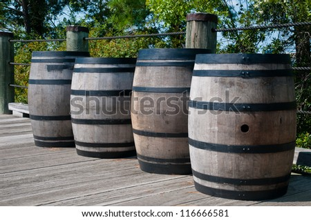 Four wooden barrels along a wooden deck.  Barrels have black metal straps around them.  They are similar to whiskey barrels, but are used for gun powder.
