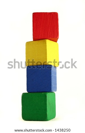 four wooden childrens blocks of different colors stacked in a high tower - low camera angle to emphasize height