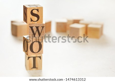 Four wooden cubes arranged in stack with text SWOT (meaning Strengths, Weaknesses, Opportunities and Threats) on them, space for text / image at down right corner