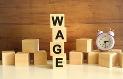 Four wooden cubes stacked vertically on a brown background form the word WAGE. Cubes are scattered nearby and there is a clock. Front View Concepts