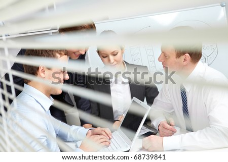 Four working businesspeople viewed from the blinds