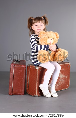 four-year beautiful girl sits on an old suitcase with a toy in hands.