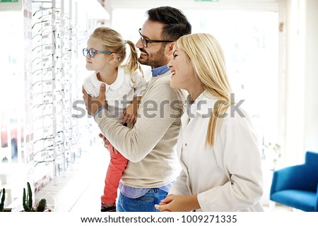 Four year little girl in optics store choosing glasses with her father. Ophtamologist helping.  #1009271335