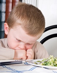 Four year old boy disliking the food on his plate