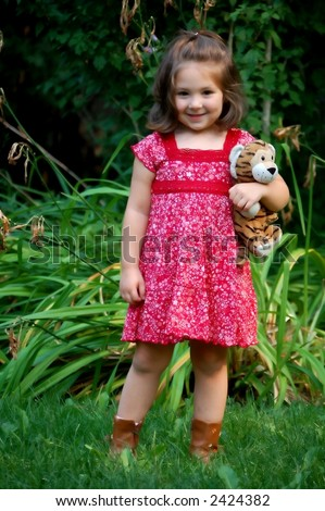 Four year old girl posing in a park with her favorite stuffed animal.