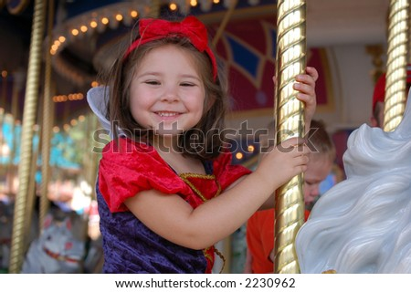 four year old girl riding a merry go round