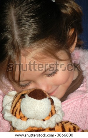 Four year old girl snuggling with her stuffed animal tiger.