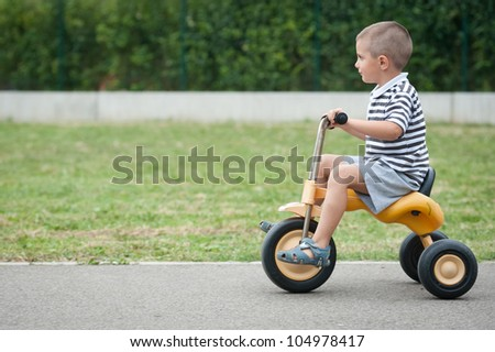Four year old kid playing outdoor on tricycle.