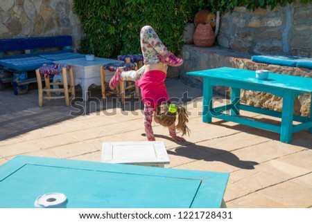 four years old blonde girl trying to do the somersault or handstand on floor of a roof with tables #1221728431