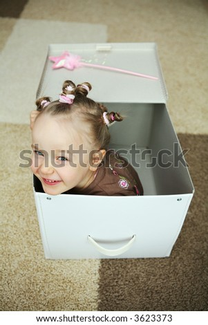 Four years old girl coming out from a carton box - stock photo