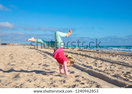 four years old little girl trying to do handstand or somersault on sandy Beach La Barrosa in Chiclana de la Frontera (Cadiz, Andalusia, Spain, Europe), with ocean on the horizon #1240962853
