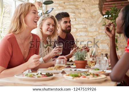 Four young adult friends eating in a restaurant, close up