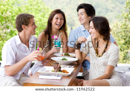 Four young adults enjoying a meal together on vacation