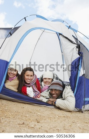 Four young adults lying down in small tent. - stock photo