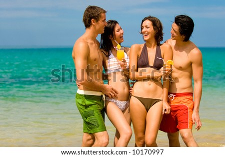 Four young adults standing by ocean with drinks